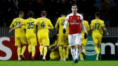 Indosport - Henrikh Mkhitaryan tertunduk lesu saat Arsenal kebobolan oleh BATE Borisov, Jumat (15/02/19).