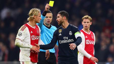 Sergio Ramos (kanan) menyalami Kasper Dolberg pasca melakukan pelanggaran. - INDOSPORT