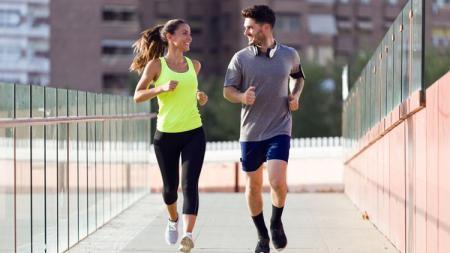 Seorang wanita dan pria sedang melakukan olahraga lari. - INDOSPORT