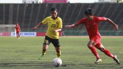 Indosport - Firza Andika (kanan) duel dengan pemain Malaysia untuk mendapatkan bola
