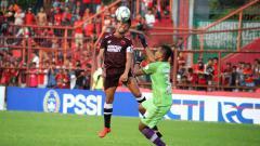 Indosport - Ferdinand Sinaga berduel di udara dengan kiper Perseru Serui, Rabu (20/02/19)
