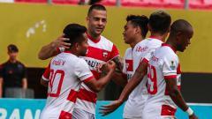Indosport - Aksi selebrasi pemain Madura United melawan Sriwijaya FC