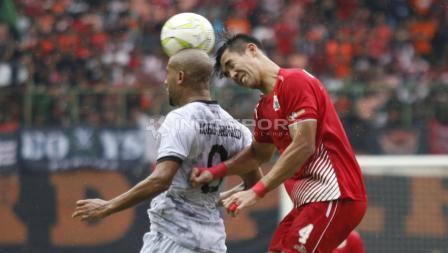 Ryuji Utomo (kanan) saat duel udara dengan striker PS Tira, Loris Arnaud pada leg kedua babak 16 besar Piala Indonesia di stadion Patriot, Kamis (21/02/18).