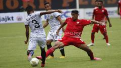 Indosport - Bruno Oliviera (tengah) mencoba merebut bola dari Abduh Lestaluhu