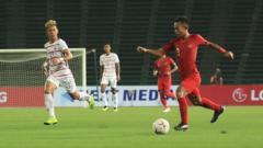 Indosport - Sani Rizki Fauzi tengah membawa bola ke arah gawang Kamboja