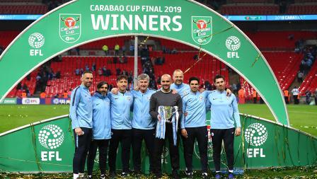 Josep Guardiola dan jajaran pelatih Man City melakukan foto bersama trofi Piala Liga Inggris
