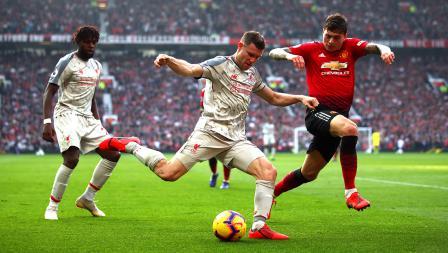Bek sayap Liverpool, James Milner (tengah) sedang berusaha memberikan umpan ke rekannya, sementara bek Man United, Victor Lindelof berusaha menghalaunya.