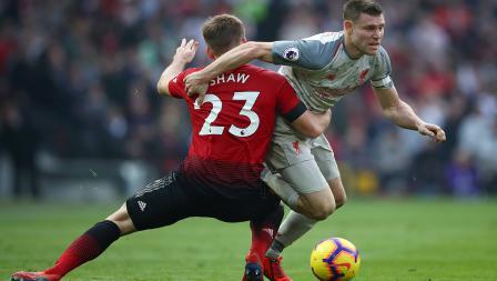 Luke Shaw menutup ruang gerak dari James Milner yang sedang membawa bola.