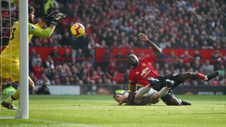 Kiper Liverpool, Alisson Becker berhasil mengamankan tendangan dari Romelu Lukaku, striker Man United.