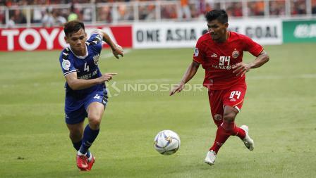 Heri Susanto (kanan) mencoba melewati adangan bek Becamex Binh Duong, Ho Tan Tai pada laga perdana Piala AFC 2019 Grup G di Stadion GBK, Selasa (26/02/18).