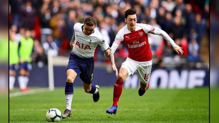 Pergerakkan dari bek sayap Tottenham Hotspur, Kieran Trippier (kiri) diganggu oleh playmaker Arsenal, Mesut Ozil.