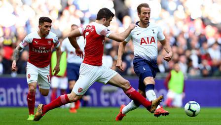 Pergerakkan dari striker Tottenham Hotspur, Harry Kane dicegat oleh bek Arsenal, Sokratis.