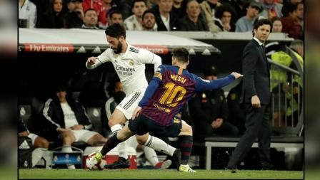 Pergerakkan dari gelandang serang Real Madrid, Isco dijegal oleh pemain megabintang Barcelona, Lionel Messi.