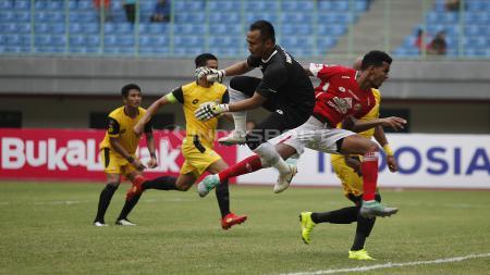 Duel antara kiper BFC, Wahyu Tri Nugroho (tengah) dengan striker Semen Padang pada laga perdana grup B Piala Presiden 2019 di stadion Patriot, Minggu (03/03/19). - INDOSPORT