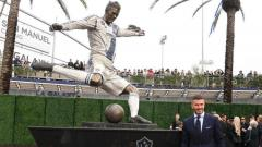 Indosport - Pesepakbola David Beckham bersama Patungnya di LA Galaxy