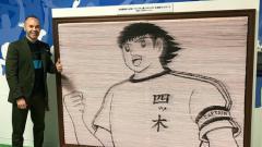 Indosport - Andres Iniesta saat berpose bersama Captain Tsubasa di Stasiun Yotsuki, Tokyo.