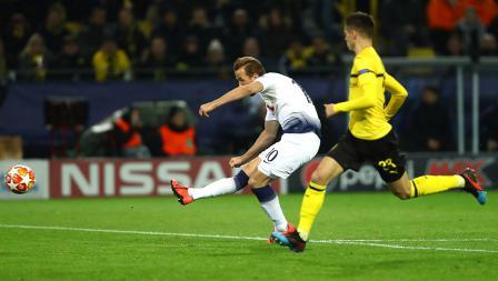 Harry Kane tengah mengeksekusi bola ke arah gawang Borussia Dortmund dan membuahkan gol pada pertandingan babak 16 besar Liga Champions 2018/19 di Stadion Westfalen, Rabu (06/03/19).