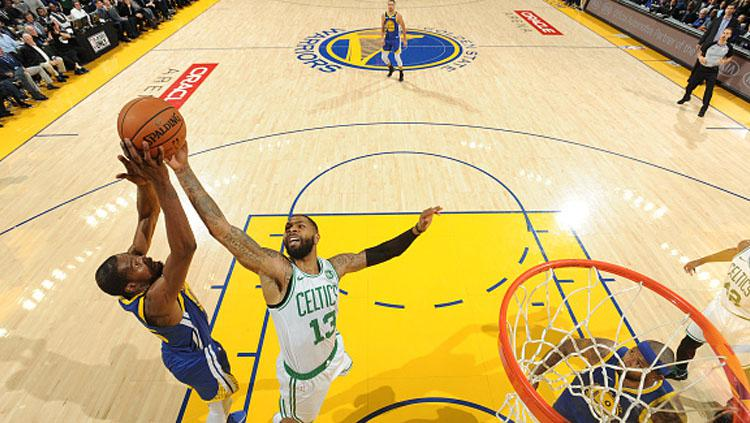 Upaya bintang Warriors, Kevin Durant (kanan) saat ingin memasukkan bola diblok oleh penggawa Celtics, Marcus Morris. Copyright: INDOSPORT