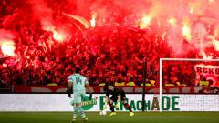 Indosport - Suporter Arsenal menyalakan flare di pertandingan melawan Rennes pada leg pertama 16 besar Liga Europa 2018/19 di Roazhon Park, Jumat (8/3/19) dini hari WIB.