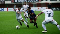Indosport - Para pemain Persija menjaga pergerakan pemain Madura United (tengah).