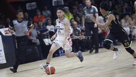 Point guard Stapac Jakarta, Widyantaputra Teja seakan sedang menggiring bola basket menggunakan kakinya. - INDOSPORT