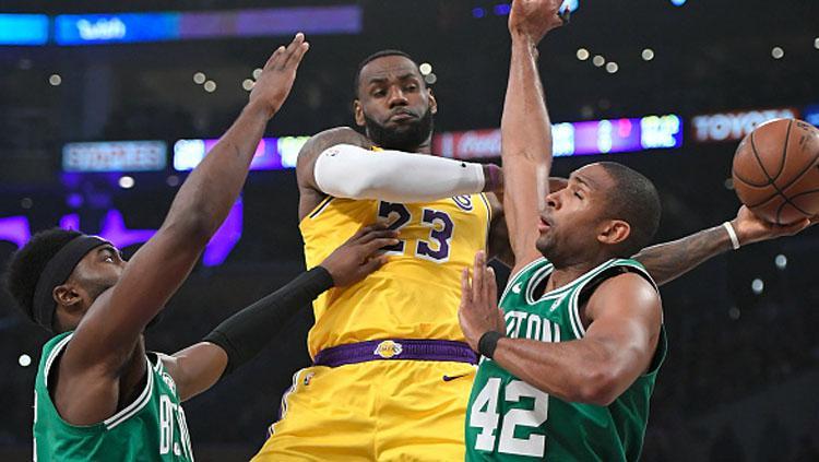 Pemain megabintang LA Lakers, LeBron James dijaga ketat oleh 2 pemain bintang Boston Celtics. Copyright: INDOSPORT