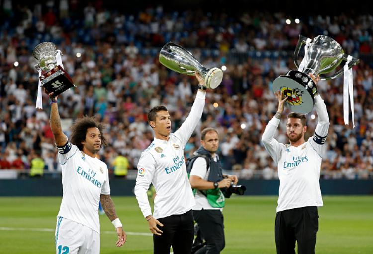 Marcelo (kiri), Cristiano Ronaldo (tengah), dan Sergio Ramos saat sama-sama mengangkat trofi untuk Real Madrid. Copyright: INDOSPORT