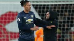 Indosport - Aksi suporter menyerang Chris Smalling di laga Arsenal vs Manchester United, Senin (11/03/19).