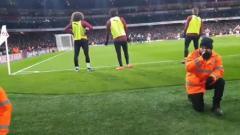 Indosport - Matteo Guendouzi dan Alex Iwobi rela merunduk di lapangan agar fans dapat menyaksikan penalti Aubameyan