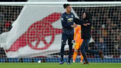 Indosport - Fans Arsenal yang menerobos masuk lapangan mendekati Chris Smalling