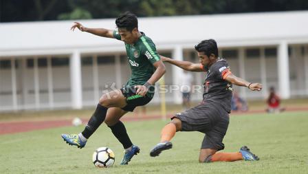 Pemain Timnas U-23, Hanif Sjahbandi (kiri) dijaga ketat oleh pemain Semen Padang pada laga uji coba di stadion Madya Senayan, Selasa (12/03/19).