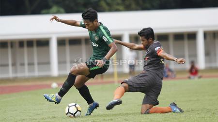 Pemain Timnas U-23, Hanif Sjahbandi (kiri) dijaga ketat oleh pemain Semen Padang pada laga uji coba di stadion Madya Senayan, Selasa (12/03/19). - INDOSPORT
