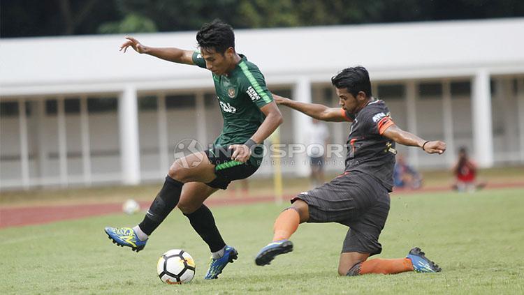 Pemain Timnas U-23, Hanif Sjahbandi (kiri) dijaga ketat oleh pemain Semen Padang pada laga uji coba di stadion Madya Senayan, Selasa (12/03/19). Copyright: Herry Ibrahim/INDOSPORT