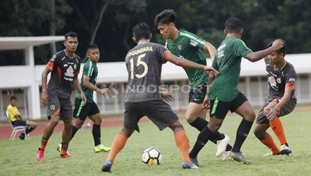Pemain Timnas U-23, Feby Eka Putra dihadang beberapa pemain Semen Padang pada laga uji coba di Stadion Madya Senayan, Selasa (12/03/19).