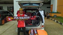 Indosport - Salah satu suporter PSM Makassar jualan disekitar Pakansari