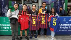 Indosport - 4 Mahasiswa memamerkan jersey Barcelona dan Timnas Spanyol yang sudah dibubuhi tanda tangan Charles Puyol, Kamis (14/3/19).