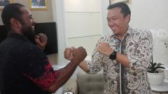 Indosport - Petinju Asal Papua, Geisler AP saat berfoto bersama Menpora RI, Imam Nahrawi.