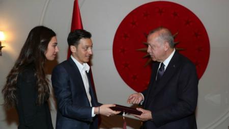 Mesut Ozil bersama sang kekasih, Amine Gulse, menyerahkan undangan pernikahan mereka pada Presiden Turki, Recep Tayyip Erdogan. - INDOSPORT