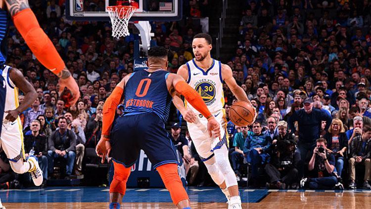 Pemain Megabintang Golden State Warriors, Stephen Curry saat ingin melewati pemain Oklahoma City Thunder, Russel Westbrook. Copyright: INDOSPORT