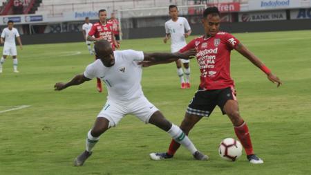 Greg Nwokolo berusaha mengambil bola dari pemain Bali United - INDOSPORT
