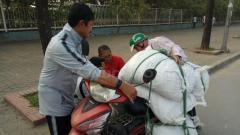Indosport - Indra Sjafri tengah membantu salah satu pengendara motor yang muatannya berlebihan di Vietnam.