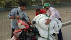 Indosport - Indra Sjafri tengah membantu salah satu pengendara motor yang muatan di Vietnam.