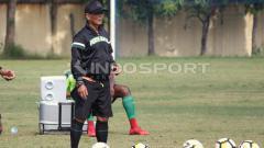 Indosport - Djadjang Nurdjaman memperhatikan pemainnya latihan di Lapangan Polda Jatim.