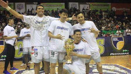 Empat pemain Stapac Jakarta melakukan sesi foto dengan trofi