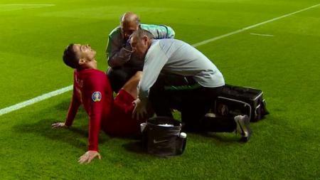 Striker Timnas Portugal Cristiano Ronaldo diperiksa dokter usai mengalami cedera di hidungnya. - INDOSPORT
