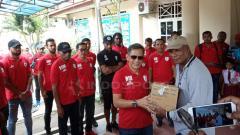 Indosport - Manajer Persipura Jayapura, Rudy Maswi didampingi para pemain Persipura saat menyerahkan bantuan ke korban banjir Sentani.