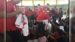Indosport - Para Pemain Persipura saat membagikan Jersey untuk para pengungsi.