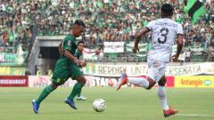 Indosport - Persebaya Surabaya Irfan Jaya saat menggiring bola dihalau pemain Tira Persikabo.