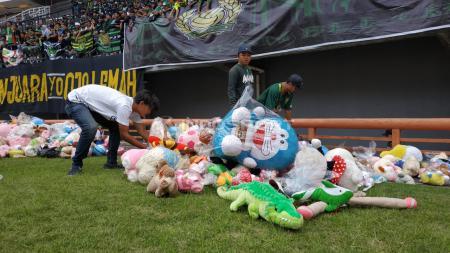 Hujan Boneka di laga Persebaya vs Tira Persikabo sebagai bentuk solidaritas untuk anak-anak penderita kanker. - INDOSPORT