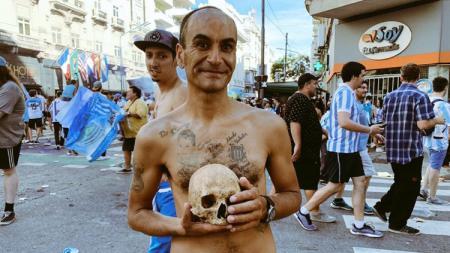 Salah seorang fans sepak bola membawa tengkorak kepala manusia. - INDOSPORT